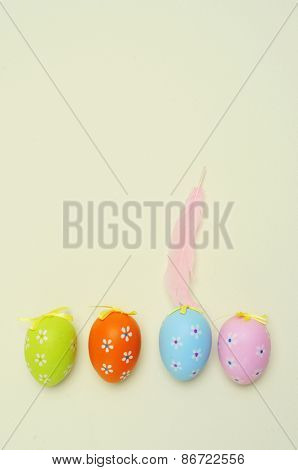 high-angle shot of some decorated easter eggs of different colors placed in line and a pink feather