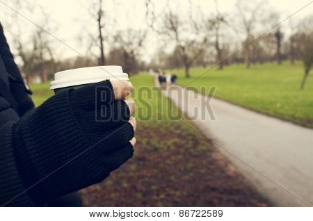 closeup of a young caucasian man very sheltered wearing fingerless gloves holds a hot drink in a paper cup in Hyde Park in winter in London, United Kingdom
