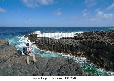 Hiker is standing on the rocky coast of El Hierro