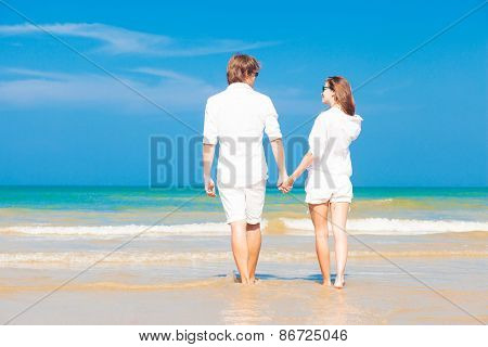 happy young couple in white clothes having fun on tropical beach