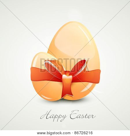 Glossy eggs binding by orange ribbon for Happy Easter celebration on grey background.