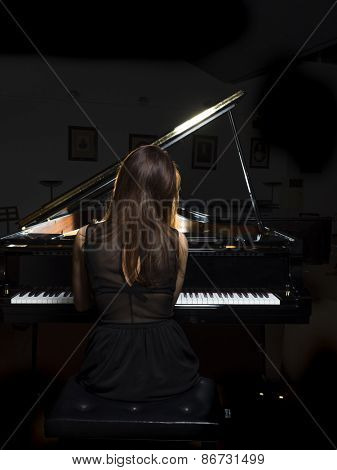 Female pianist performing on a grand concert piano