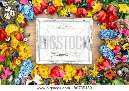 Holidays Background With Spring Flowers, Easter Eggs And Wooden Desk