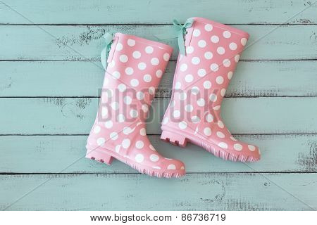 Pink polka dot shoes on mint shabby chic wooden background, top view point