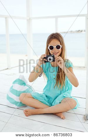Preteen child resting and taking photos at the beach in summer