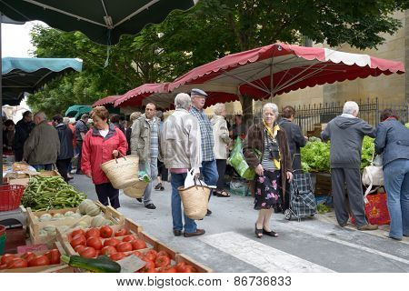 BERGERAC, FRANCE - JUNE 29, 2013: People on the street farmers market on the Market square. Farmers market near the Notre Dame church is open every Wednesday and Saturday