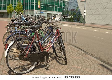 EINDHOVEN, NETHERLANDS - JUNE 23, 2013: Bicycle parking against the futuristic The Blob building. The bike is considered as an element of real Dutch life