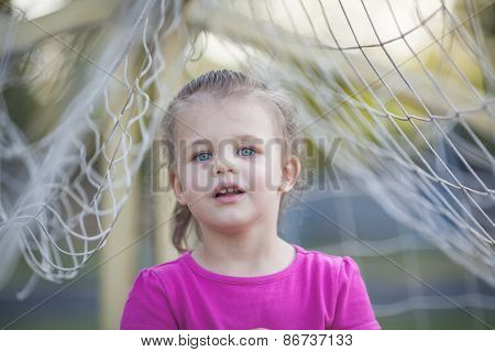 Little girl between football net