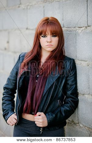 Rebellious teenager girl with red hair very angry leaning on a wall