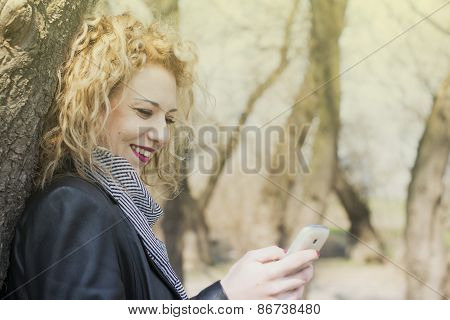 Young Curly Blond Woman Typing On The Phone In Outdoors