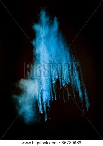 Freeze motion of blue dust explosion isolated on black background