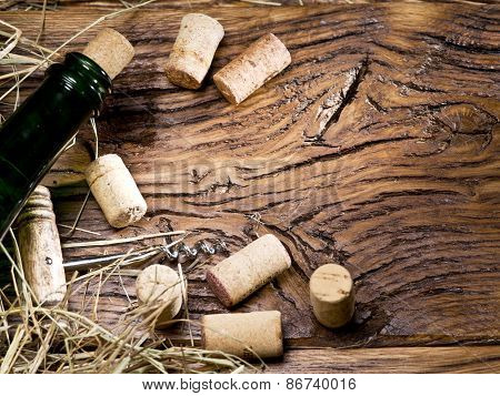 Wine bottle and corks on an old wooden table.