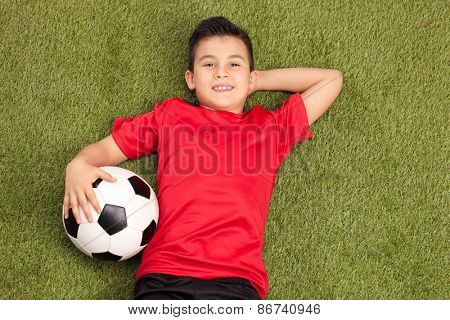 Relaxed youngster in a red football jersey lying on a pitch, holding a football in his hand and looking at the camera