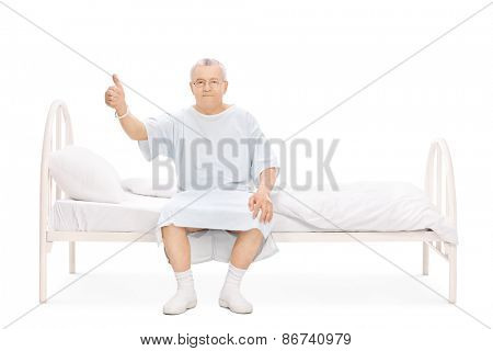 Studio shot of a mature patient sitting on a hospital bed, giving a thumb up and looking at the camera isolated on white background