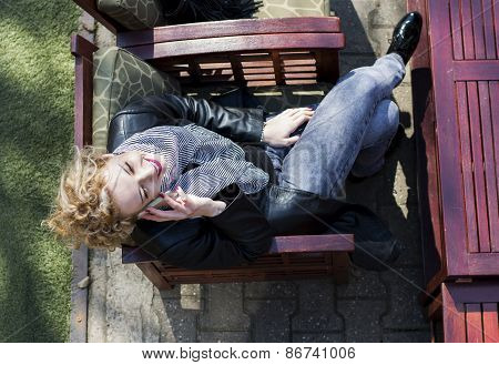 Young Curly Blond Woman Talking On The Phone In Cafe