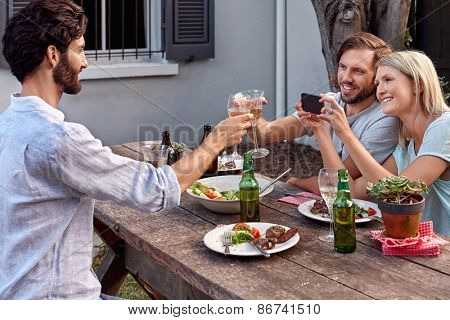 group of friends drinking cheers taking picture photos on mobile cellphone camera at outdoor garden party