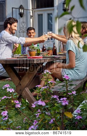 Group of friends toasting to celebration with wine drinks at garden outdoors party