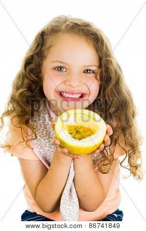 Cute little preschooler girl holding a passion fruit half