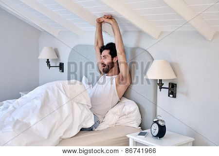 exhausted man stretching arms early morning after waking up from comfortable bed at home