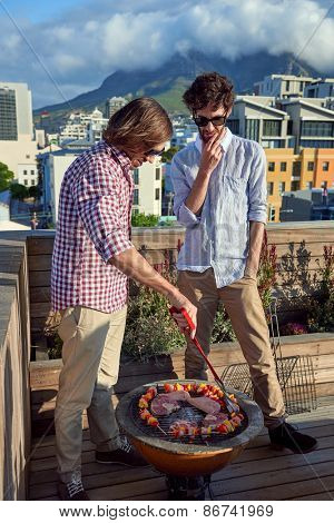 Friends having a barbecue on outdoor rooftop terrace with skewer kebabs