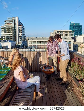 Friends having a barbeque on the outdoor rooftop terrace with skewer kebabs