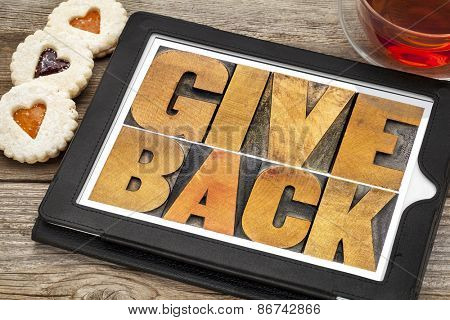 give back words text in letterpress wood type on a digital tablet with tea and heart cookies