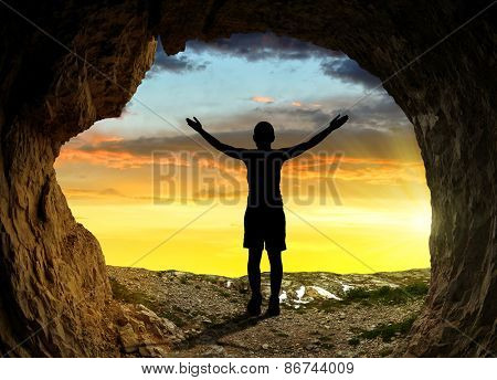 Silhouette of a girl standing in front of the entrance to the cave