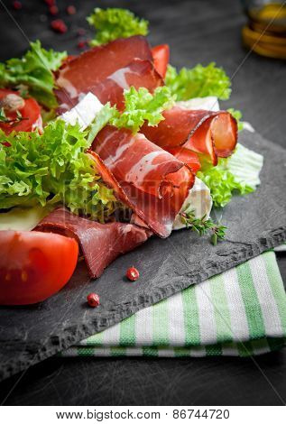 Prosciutto salad with cheese and tomatoes on a plate of natural slate