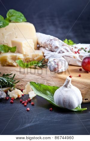 Various cheeses and salami on the wooden board