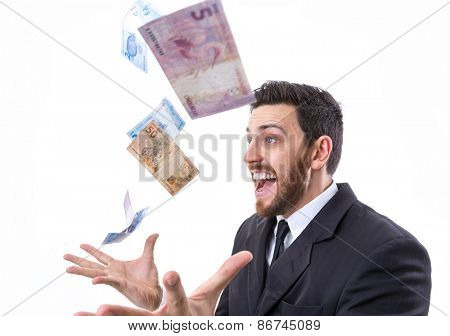 Happy young man in a rain of Brazilian Money
