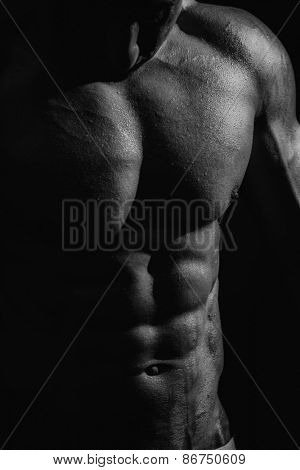 black and white studio shoot of strong athletic man on dark background