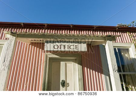 Low angle view of old pink corrugated iron building  with Office sign over entrance.