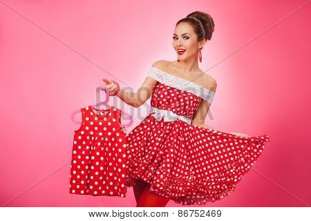 Happy Woman Holding Up Kidswear. Pin-Up Retro Style.