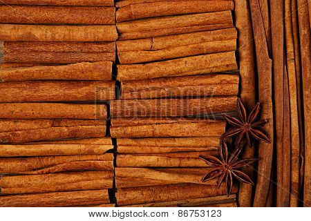Cinnamon sticks and anise star on wooden background full frame