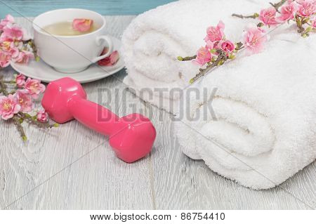 Healthy living concept - hand weight, towels and green tea