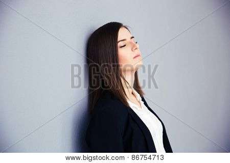 Tired businesswoman with closed eyes leaning on the gray wall