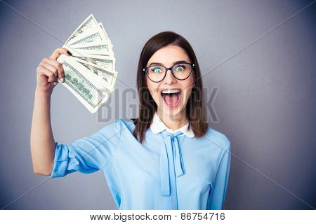 Laughing businesswoman holding bills of dollar over gray background. Wearing in blue shirt and glasses. Looking at camera