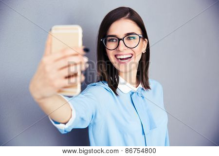 Laughing businesswoman making selfie photo on smartphone. Wearing in blue shirt and glasses. Standing over gray background