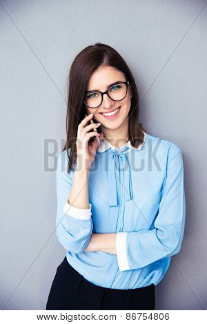 Smiling businesswoman talking on the phone over gray background. Wearing in blue shirt and glasses. Looking at camera