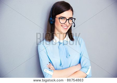Happy businesswoman with headset and arms folded standing over gray background. Wearing in blue shirt and glasses. Looking at camera