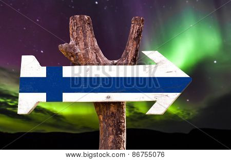 Finland flag wooden sign with northern lights background