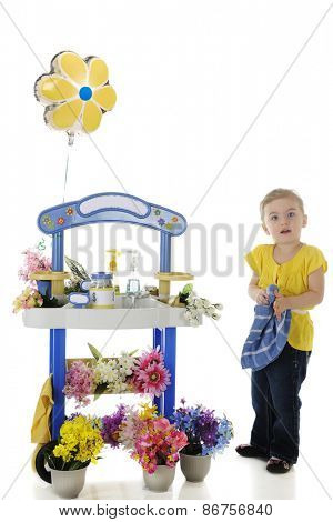 An adorable preschooler looking at viewer as she wipes her hands on a towel as tending her flower stand.  Signs on the stand left blank for your text.  On a white background.