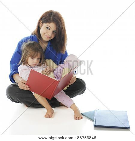 An attractive teen volunteer reading a book to a sad little girl.  On a white background.