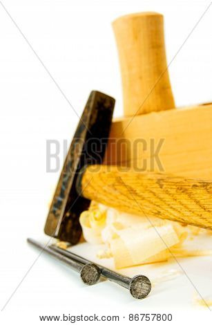 Joiner's works. Wooden shaving, hammer, nails and plane on white background.
