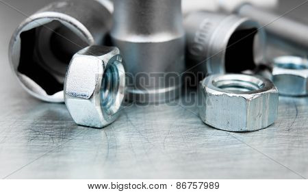 Wrench heads and nuts on scratched metal background.