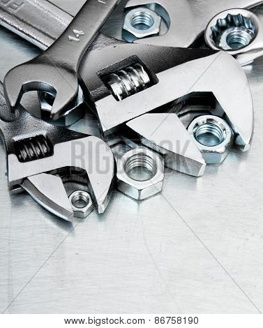 Wrenches and nuts on the scratched metal background.