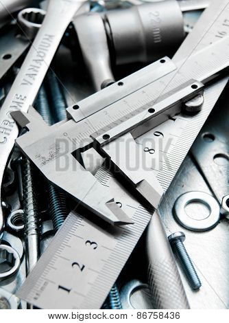 Caliper and tools on the scratched metal background.
