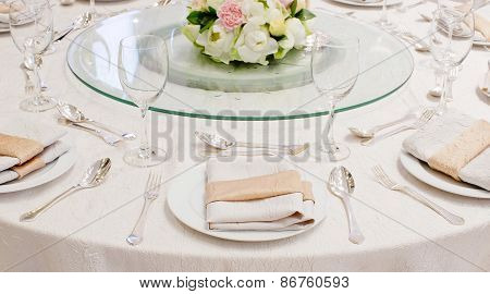 The Table Is Set For A Western Style Dinner With Round Glass On Table