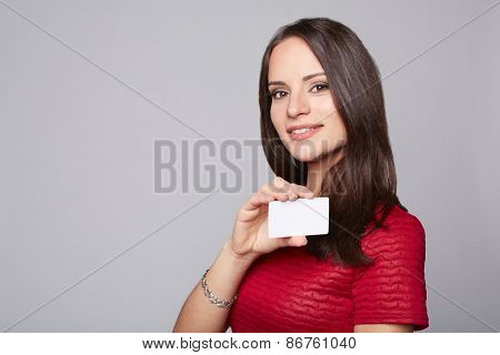 Portrait of young smiling business woman holding credit card isolated on gray background