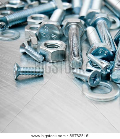 Nuts, screws and bolts on scratched metal background.